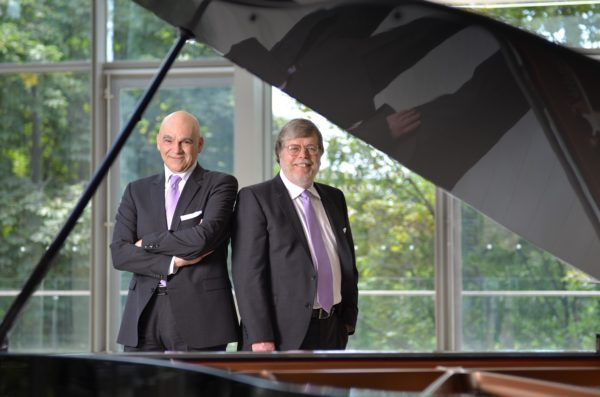 A photo of the piano duo Anagnoson and Kinton, posing by a grand piano.